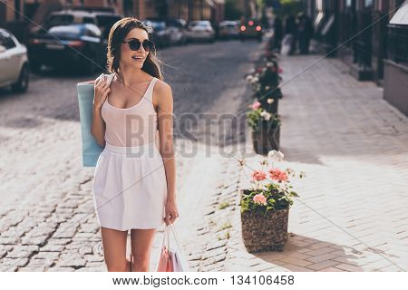 Great day for shopping! Beautiful young woman carrying shopping bags and looking away with smile while walking along the street