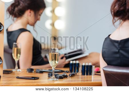 Closeup of glass of champagne standing on the table near young woman reading magazine in dressing room