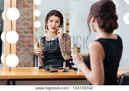 Charming young woman drinking champagne and talking on mobile phone in dressing room
