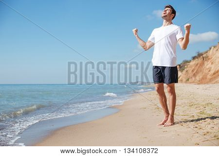 Happy excited young man with raised hands standing and celebrating success on the beach