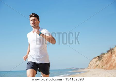 Attractive young man in white t-shirt and black shorts running along the beach