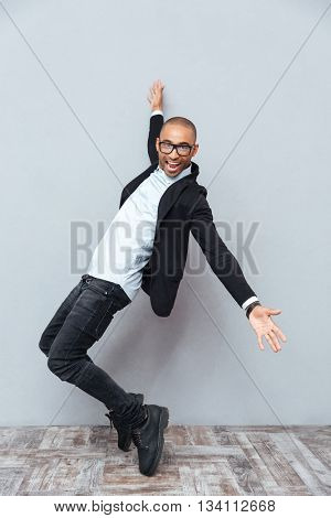 Full length of cheerful african american young man in glasses dancing