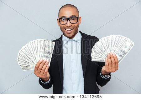 Smiling successful african young man holding a lot of money in both hands