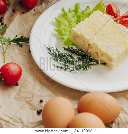 Close up omelet with ham on parchment background. Vegetable composition