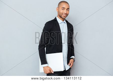 Handsome african american young man standing and holding laptop