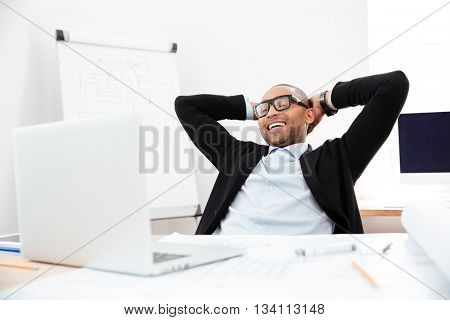 Successful relaxed young businessman sitting back in his chair with hands clasped behind his neck
