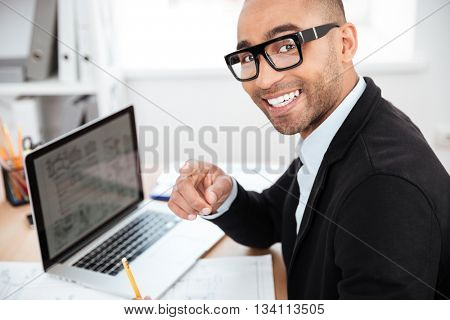 Close-up of smiling smart young businessman working with computer looking at camera in office