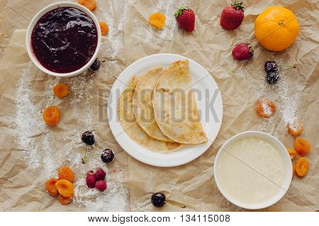 Pancakes with jam and berries on parchment background