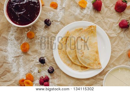 Pancakes with jam and berries on parchment background. Flat Lay.