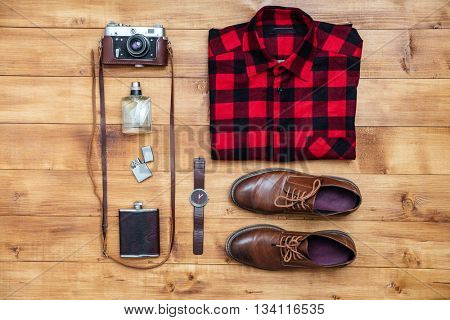 Travel concept - shirt, camera, shoes, flask, lighter, watch and perfume on the desk