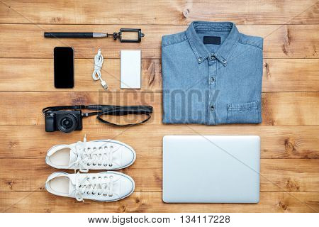 Travel concept shoes, shirt, mobile phone, laptop,mp3, usb, camera, selfie stick on the desk