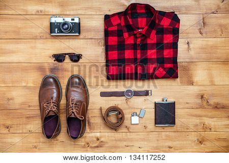 Travel concept - shirt, camera, shoes, flask, lighter,eyeglasses, watch and wallet on the desk
