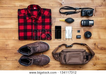 Travel concept boots, shirt, camera, mobilephone, mp3, earphones, bag on the desk