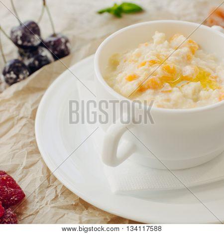 Close up millet porridge with pumpkin. Parchment background.