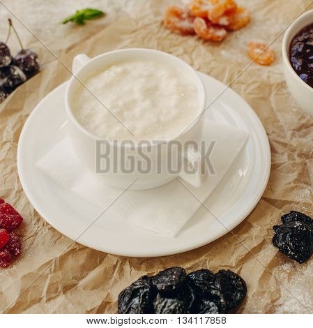 Rice porrige with berries on parchment background.