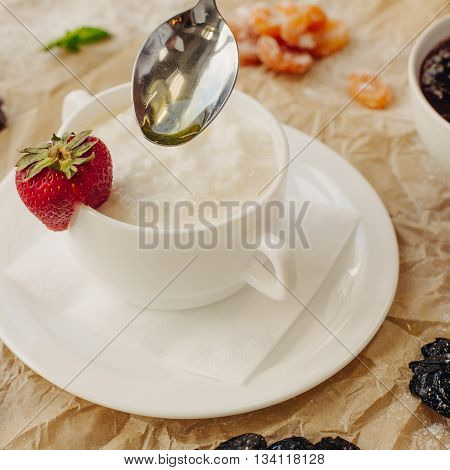 Rice porrige with strawberry on parchment background