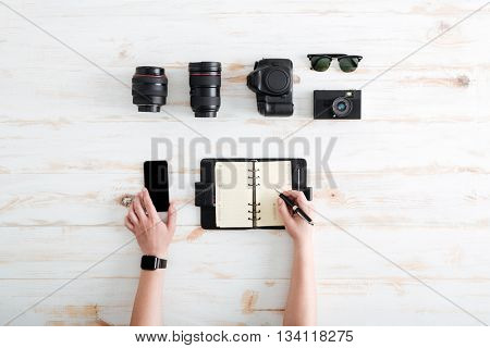 Hands of young man writing in notebook and using blank screen mobile phone on wooden table with sunglasses, lenses and photo camera