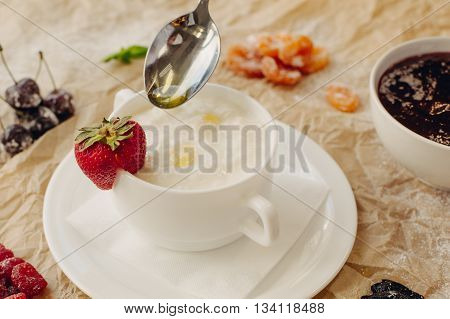 Rice porrige with strawberry and oil spoon on parchment background.