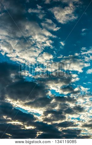 Cumulus sunset clouds with sun setting down the beautiful sky