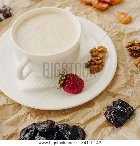 Oat meal with walnuts and berries. Parchment background. Square crop