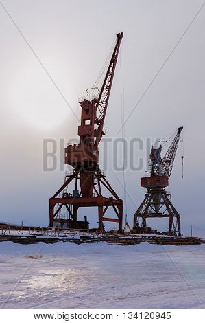 Ships cargo cranes on the shore of Lake Baikal in winter at sunset.