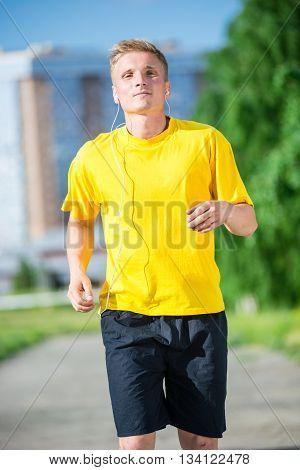 Running man jogging in city street park at beautiful summer day. Sport fitness model caucasian ethnicity training outdoor. Jogger listening training music on smartphone