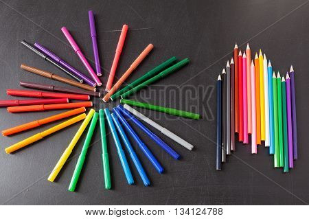 A lot of colorful felt-tip pens in circle and colorful pencils in row on the black school chalkboard as background concept