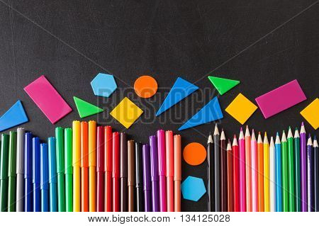 A lot of colorful felt-tip pens and colorful pencils in row and geometric figures on the black school chalkboard as background concept