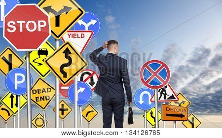 Businessman is confused due to a lot of road signs, tries choosing the right direction for further actions. On sky background.