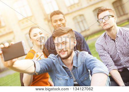 Happy friends are making selfie near a university. They are sitting on grass and resting. Man and woman are looking at mobile phone and laughing