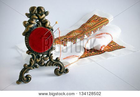 An antique pincushion in a bronze frame with angels against the background of embroidery with vignetting effect