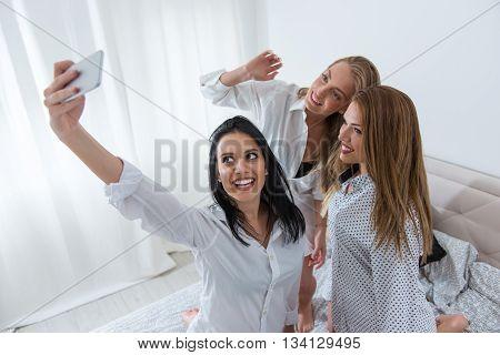Girls making a crazy selfie with selfie stick.