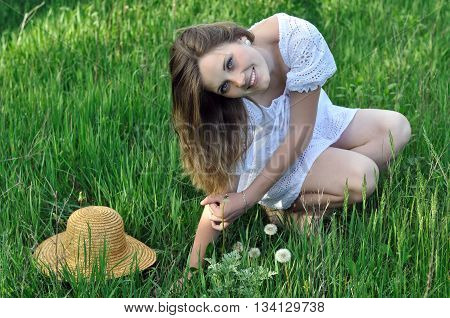 portrait of a teenage girl among the green grass in the meadow
