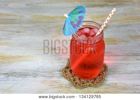 Fruit punch drink in glass mason jar with paper umbrella and gingham straw on rope coaster.