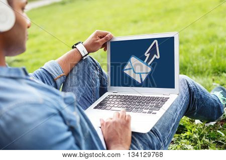 Attractive young man is relaxing in the nature. He is sitting on grass and holding a laptop. The student is listening to music from headphones with pleasure