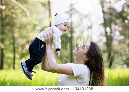 mom throws up his young son in the park