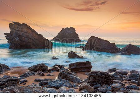 Ocean Landscape with big rocks at beautiful Sundown time