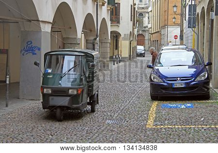 Someone Is Driving A Motor Tricycle On Narrow Street In Padua