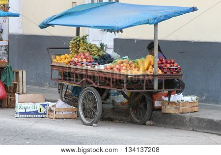 Cajamarca Peru - June 11 2016: Andean woman sells fruit from fruit cart in Cajamarca Peru on June 11 2016