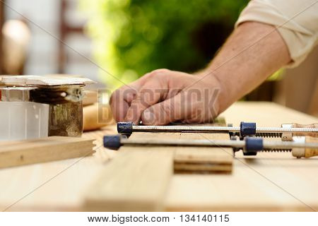 Carpenter hands at work with clamps selective focus