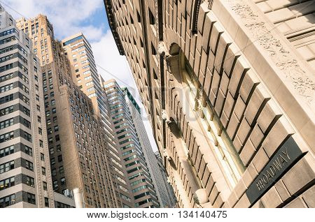 Tilted composition of high buildings and skyscrapers in Broadway district - Architectural concept of New York City in Manhattan downtown - Lower view of the skyline of world famous american metropolis