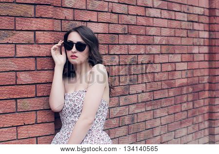 girl with red lips in the black glasses and in the sundress on the brick wall background