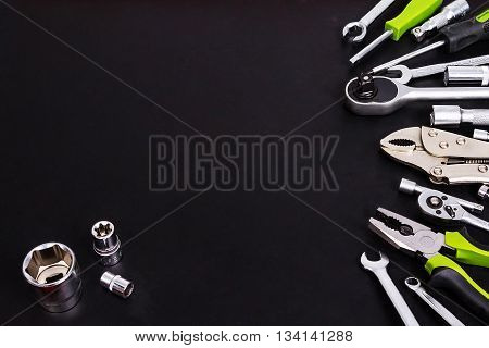 Wrench, screwdriver, pliers, pliers, extension cords, ratchet handle from the right side on a black background . Three socket wrenche in the lower left corner on a black background .