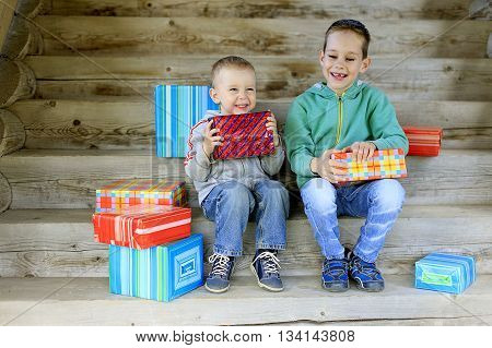 kids exchange gifts. Two cute boys are excited and look forward to how open gifts
