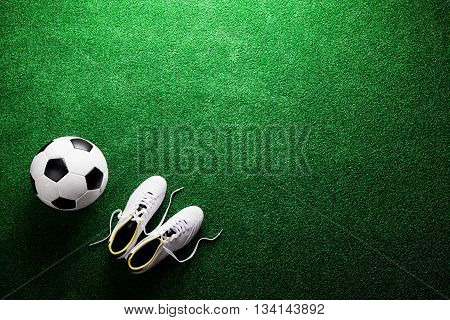 Soccer Ball And Cleats Against Green Artificial Turf, Studio Sho