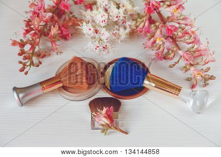 There White and Pink  Branches of Chestnut Tree with Open Blue and Golden Jar of Cream are on White Table,Selective Focus.Toned