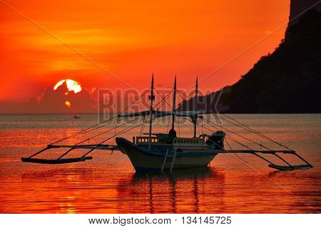Traditional filippino boat at El Nido bay in sunset lights. Palawan island, Philippines