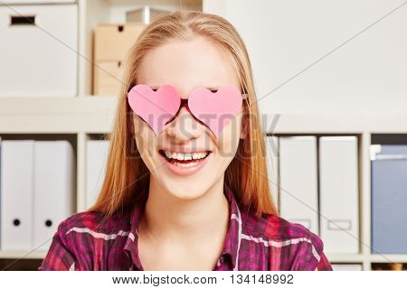 Woman with two pink harts in front of her eyes onr her glasses