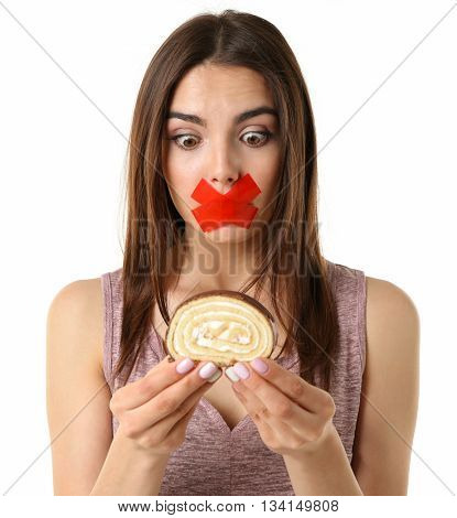 Woman with tied mouth holding cake isolated on white