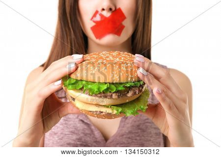 Woman with tied mouth holding hamburger isolated on white